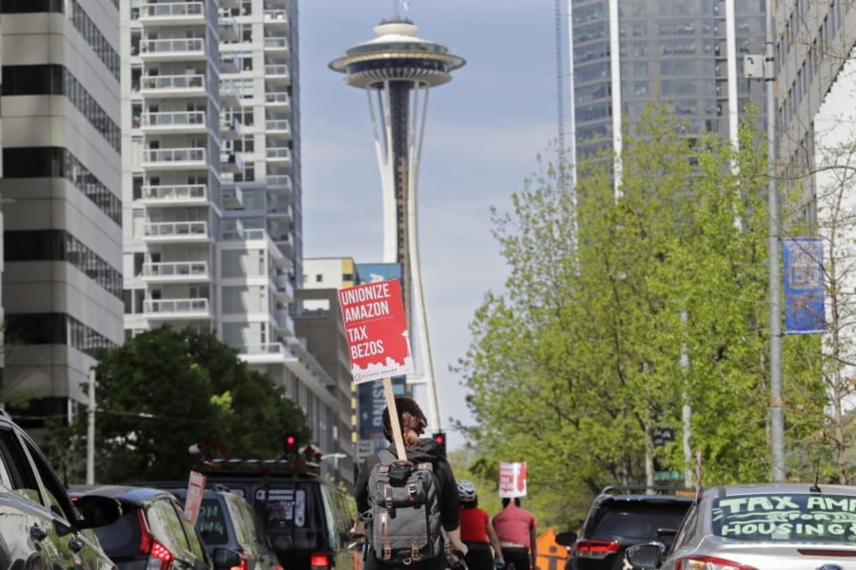 "A protester carries a sign that reads ""Unionize Amazon Tax Bezos,"" while riding a bike during a car-based protest Friday, May 1, 2020, at the Amazon Spheres in downtown Seattle. May Day in Seattle traditionally brings large protests and demonstrations from many groups and causes, and this year some people stayed in their cars or otherwise tried to practice social distancing due to the outbreak of the coronavirus. (AP Photo/Ted S."