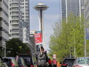 """A protester carries a sign that reads """"Unionize Amazon Tax Bezos,"""" while riding a bike during a car-based protest Friday, May 1, 2020, at the Amazon Spheres in downtown Seattle. May Day in Seattle traditionally brings large protests and demonstrations from many groups and causes, and this year some people stayed in their cars or otherwise tried to practice social distancing due to the outbreak of the coronavirus. (AP Photo/Ted S."""