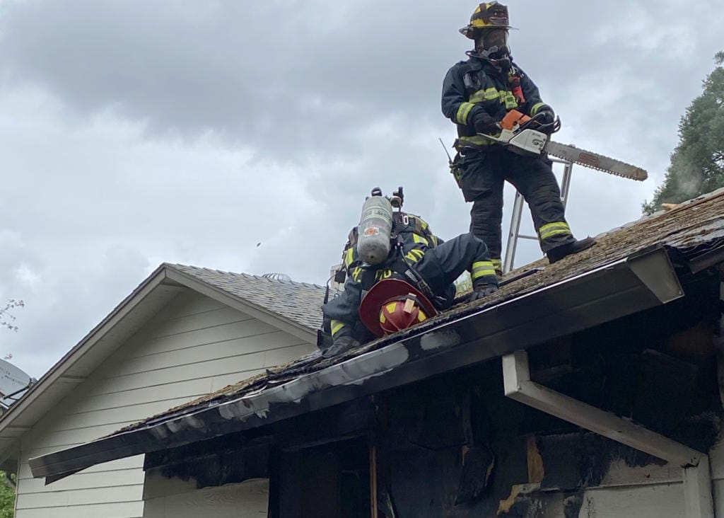 Vancouver Fire Department firefighters inspect the attic space of a garage that caught fire Monday.
