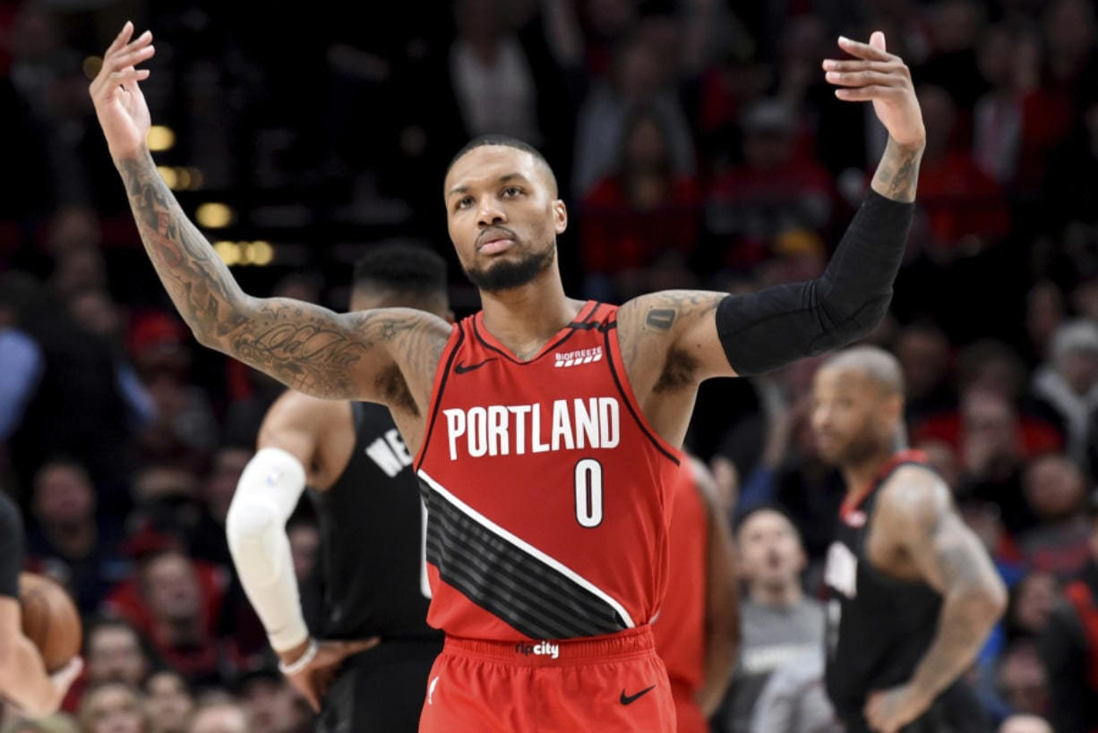 Portland Trail Blazers guard Damian Lillard urges on the crowd after scoring during the second half of the team's NBA basketball game against the Houston Rockets in Portland, Ore., Wednesday, Jan. 29, 2020. The Blazers won 125-112.