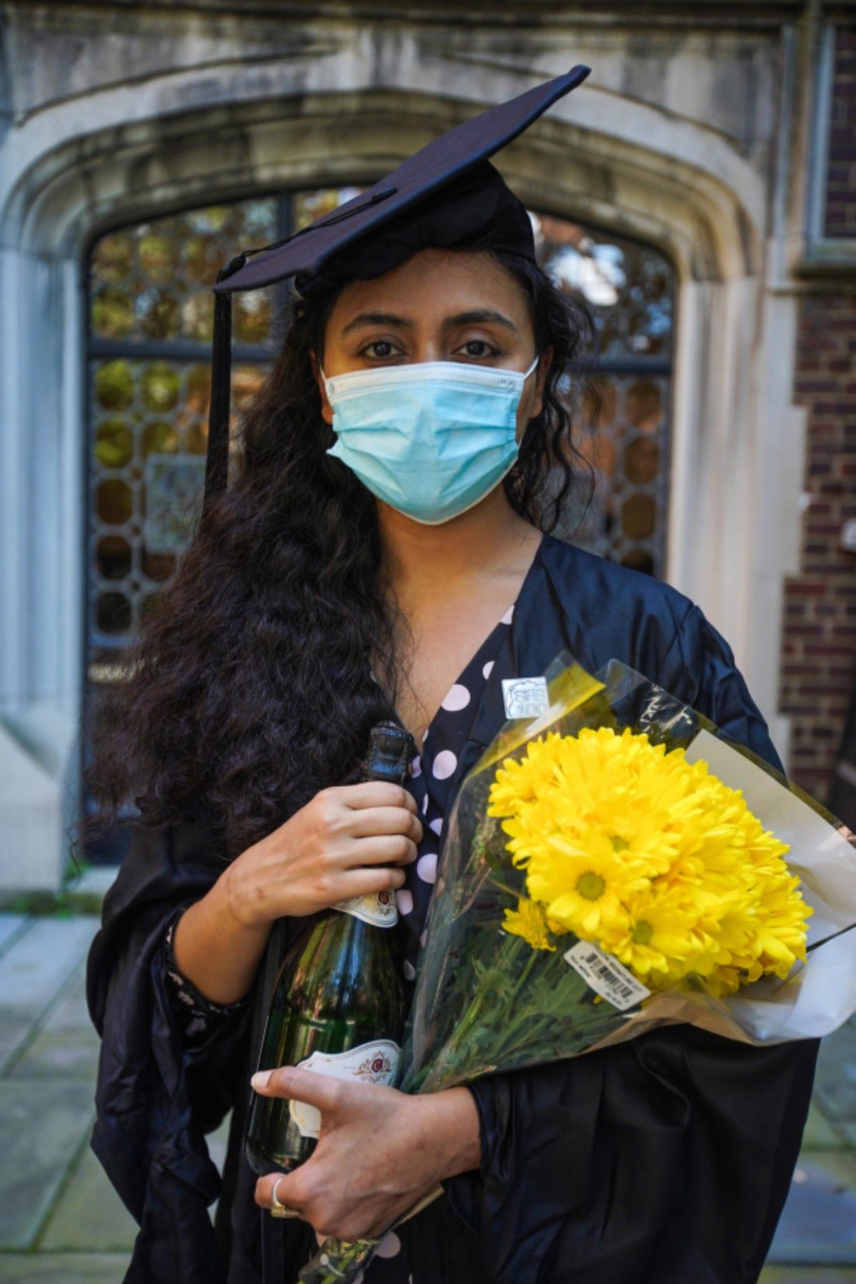 La pakistanI Varsha Thebo, de 27 aOos, posa en el campus de la International Student House donde reside, el dIa de su graduaciJPYn de la Universidad de Georgetown en Washington DC, el 15 de mayo de 2020. Varsha estudiJPY Desarrollo Humano Global, su ceremonia de graduaciJPYn fue cancelada debido a la pandemia de coronavirus, por lo que est. celebrando en lInea en su lugar.