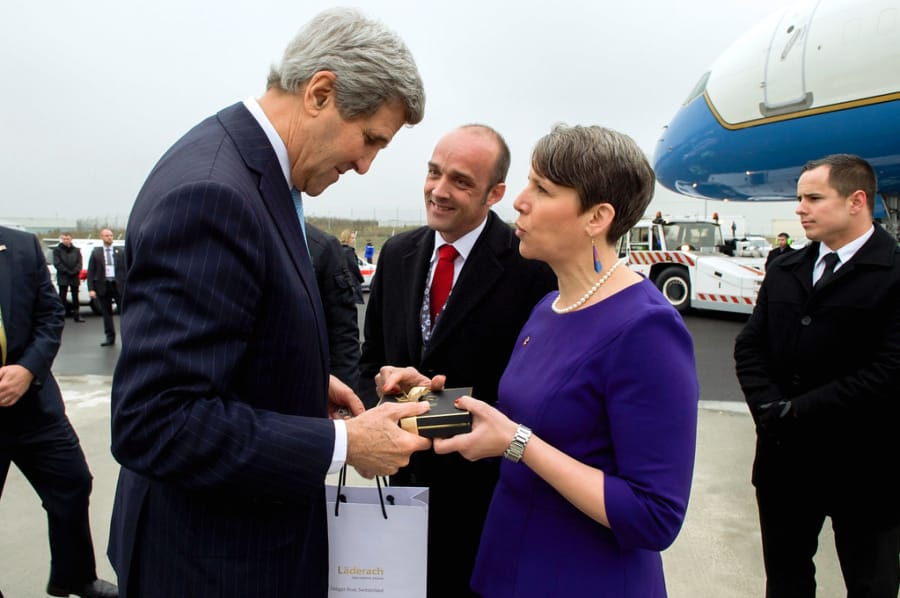 Then-Ambassador Suzi LeVine presents Secretary of State John Kerry with a box of chocolates as he departs Switzerland en route to the United Kingdom in 2014. (U.S.
