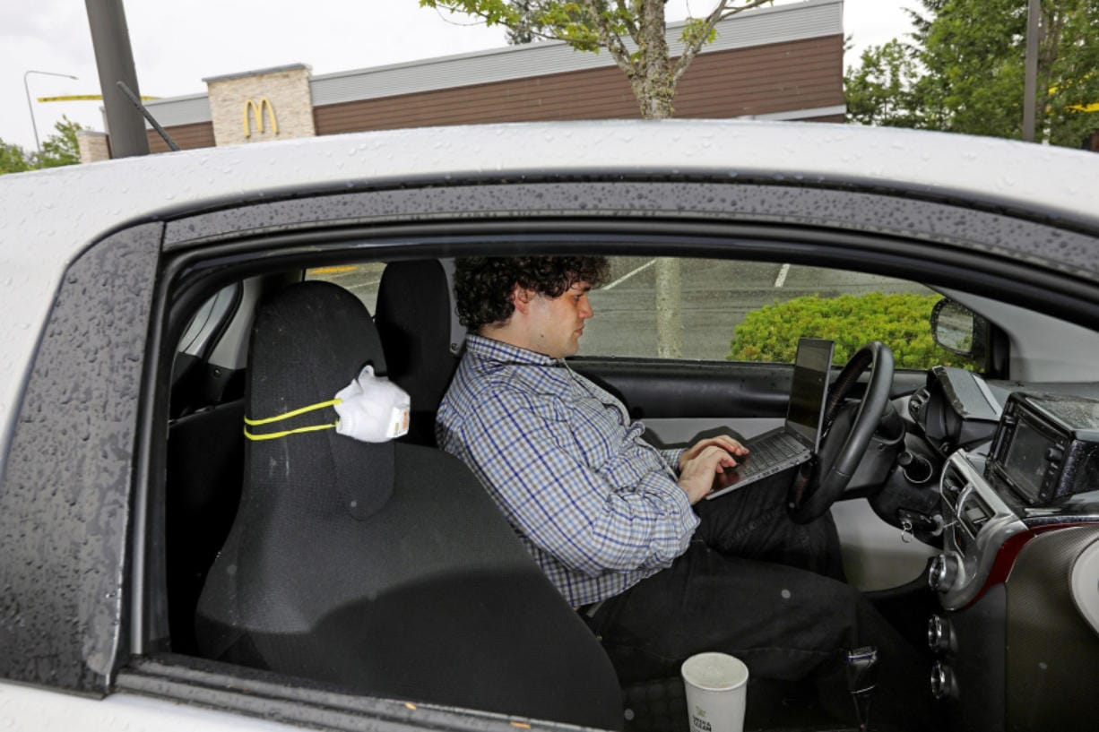 Often working from inside a car, Alex Audretsch uses a McDonald's Wi-Fi to download 40 gigs of data for his job, Tuesday, June 2, 2020 in Redmond. Audretsch represents a portion of the population with rural connectivity problems and is without access to internet at his home. In order for him to maintain his software developer job during this pandemic, he's had to take out a separate family plan through Verizon that has multiple hotspots.