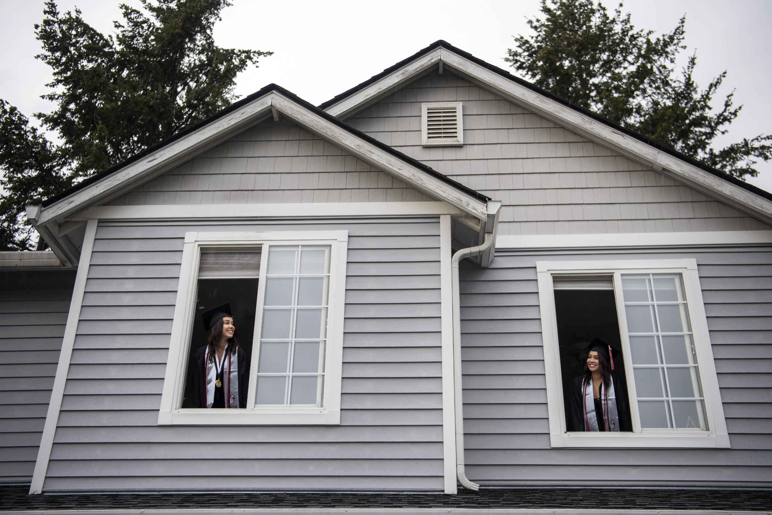Union High School seniors Lauryn Lopez, left, and her twin sister Ashtyn look out the windows of their Vancouver home.  (Alisha Jucevic/The Columbian)