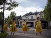 Mahealani Mackenzie, 20, left, Maile Taute, 16, Ellie Buss, 15, and Amaya Yoshinobu, 14, perform hula during a driveway concert in front of Kaloku Holt's home in Whipple Creek.