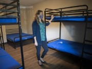 Amy Reynolds, deputy director of Share, looks over one of the newly renovated rooms at Share Orchards Inn. The shelter received new metal bed frames to help prevent bed bugs, which have been an issue in the past.