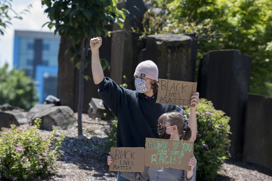 Demonstrators who declined to be identified protest against the death of George Floyd outside Vancouver City Hall on Monday.