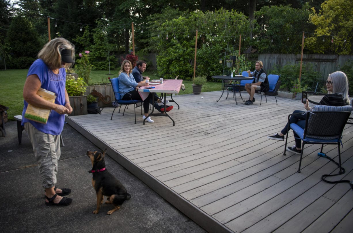 Laura Kok feeds her daughter's dog Zero as the family enjoys dinner together outside their home in Vancouver earlier this month. Since the pandemic stay-home orders were issued in March, the family has been coming together in Laura and Jeroen Kok's backyard for a socially distanced dinner at least once a week. Their youngest daughter, who lives out of town, joins via an online video call.