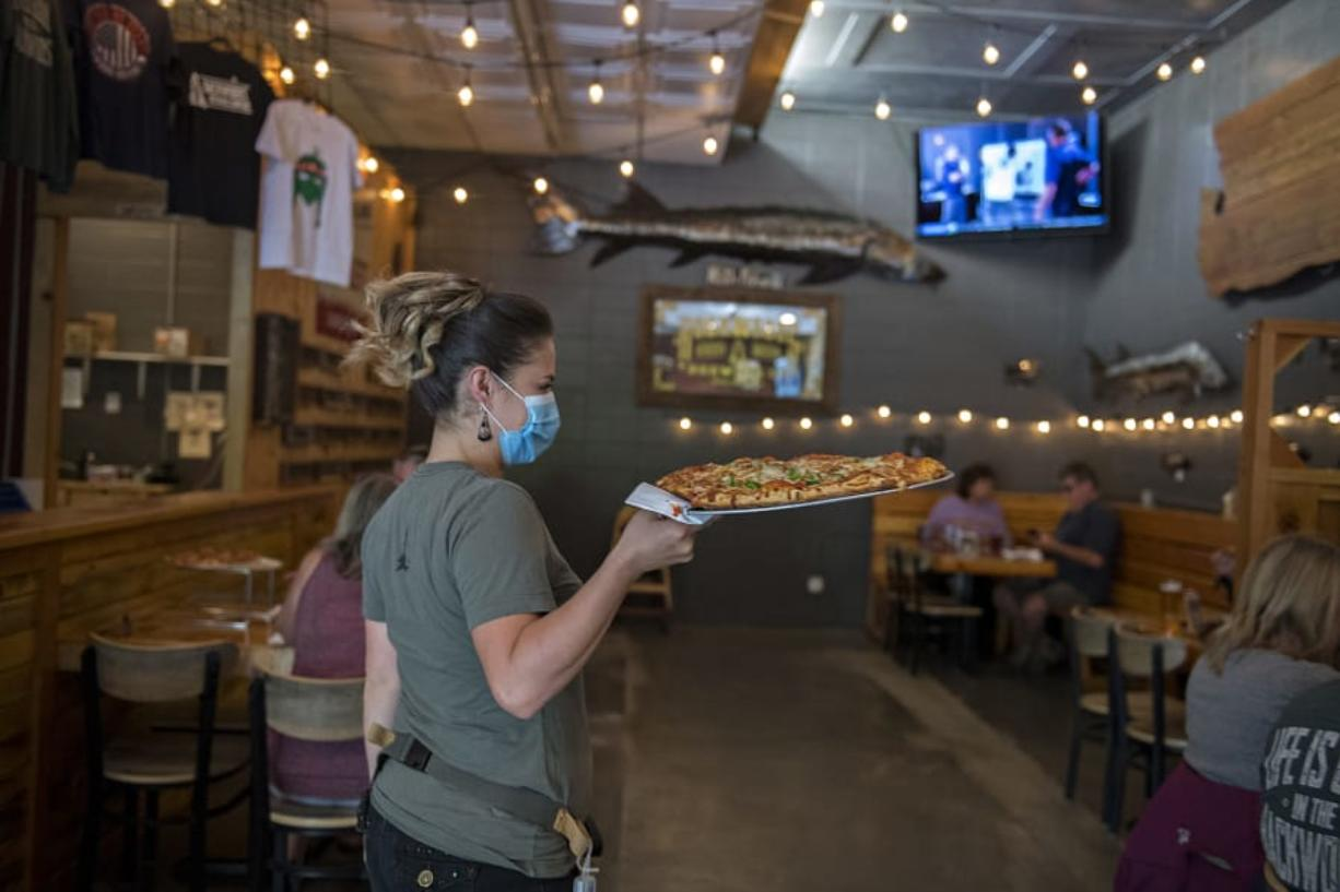 Crystal Badley of Backwoods Brewing Company wears a protective mask as she serves a fresh pizza to customers in Carson on Thursday afternoon. Carson, which is located in Skamania County, is already in Phase 2 of the reopening plan outline by Gov. Jay Inslee during the COVID-19 pandemic.