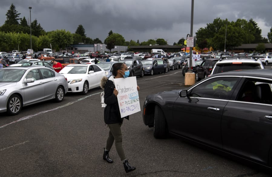 "Jaylah Morton of Vancouver, 17, helps direct traffic as cars line up for ""Car Rally For Black Lives,"" which started at the Town Plaza Center in Vancouver on Saturday. ""It makes me feel good that people are finally coming together and it's not just Black people, it's everybody,"" she said."