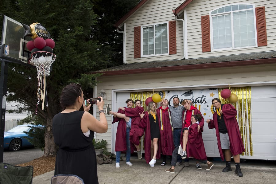 Prairie High School graduates pose for a playful photo with their former principal, Travis Drake, gray shirt, in Orchards on Friday evening. (Amanda Cowan/The Columbian)