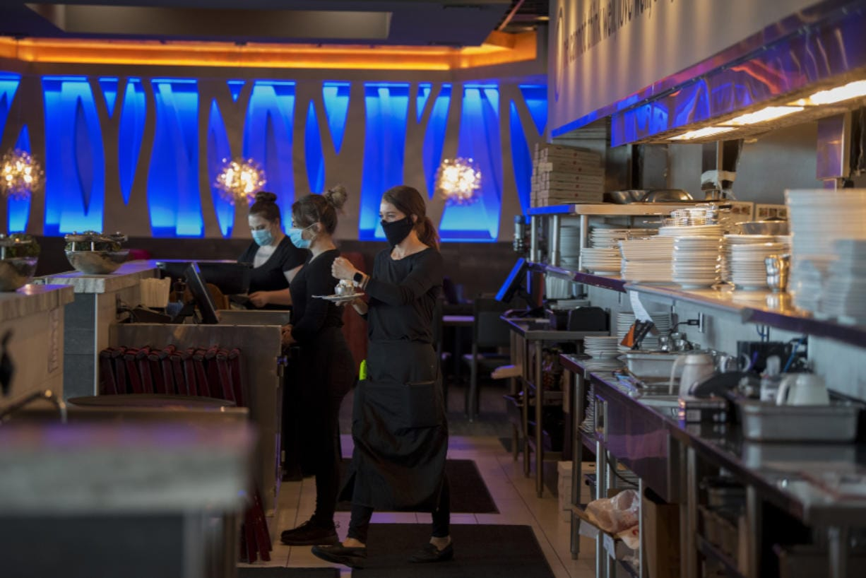 Twigs Bistro employee Bailey Gray, center, prepares to serve ice cream with a candle for a customer's birthday. Servers are wearing masks to reduce transmission of the novel coronavirus.