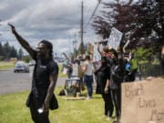 Matthew Young of Vancouver Elite Outreach, left, joins fellow demonstrators Wednesday as they rallied for black lives outside Evergreen High School.