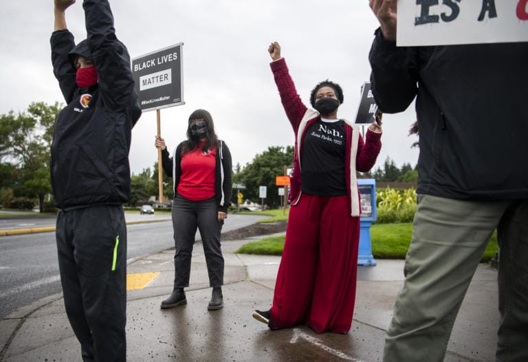 Jack Curtis of Vancouver, 10, left, and Mill Plain Elementary School first grader teachers Corinne Contreras, center, and Carmela Lemon, right, join the Black Lives Matter Rally Day of Action organized by the Washington Education AssociationÕs statewide day of events in Vancouver on June 12, 2020.