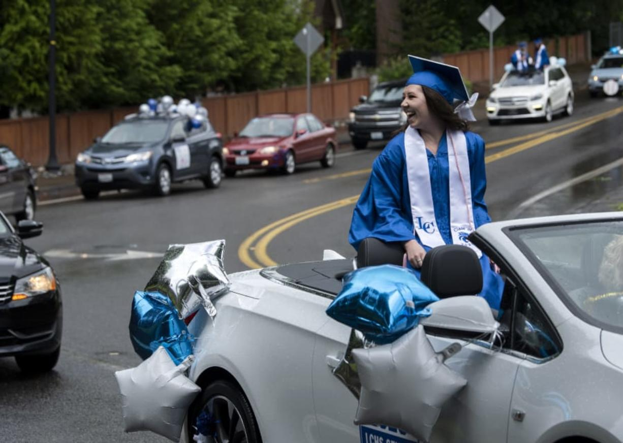 La Center High School graduate Dayna Hines rides through the car parade graduation celebration in La Center on Saturday. In lieu of an in-person ceremony, students participated in a parade through the city. The COVID-19 pandemic forced the cancellation or delay of graduation events across the state, but schools are finding creative ways to celebrate their students.