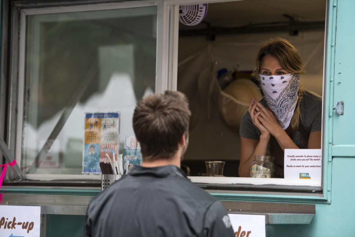Funky Fresh Juice co-owner Rebekah Trigg, right, helps customers at the Vancouver Farmers Market in downtown Vancouver. As Clark County applies to enter Phase 3 of reopening, masks are required across the state.