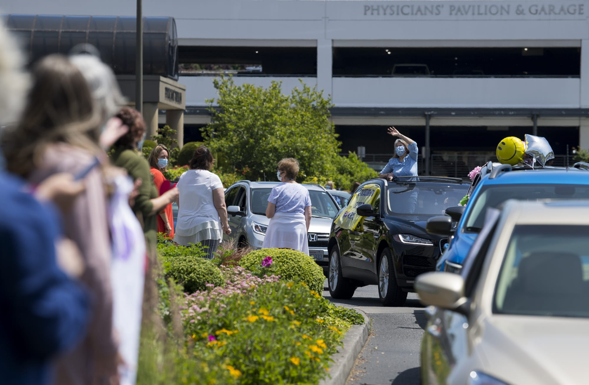 Vivian DiGioia of the stroke/brain support group, center in blue, greets hospital staff during a motorcade welcoming back volunteers at PeaceHealth Southwest Medical Center on Thursday afternoon, June 18, 2020. Around 40 volunteers, who have been furloughed since March 18, came out for the warm welcome back. (Amanda Cowan/The Columbian)