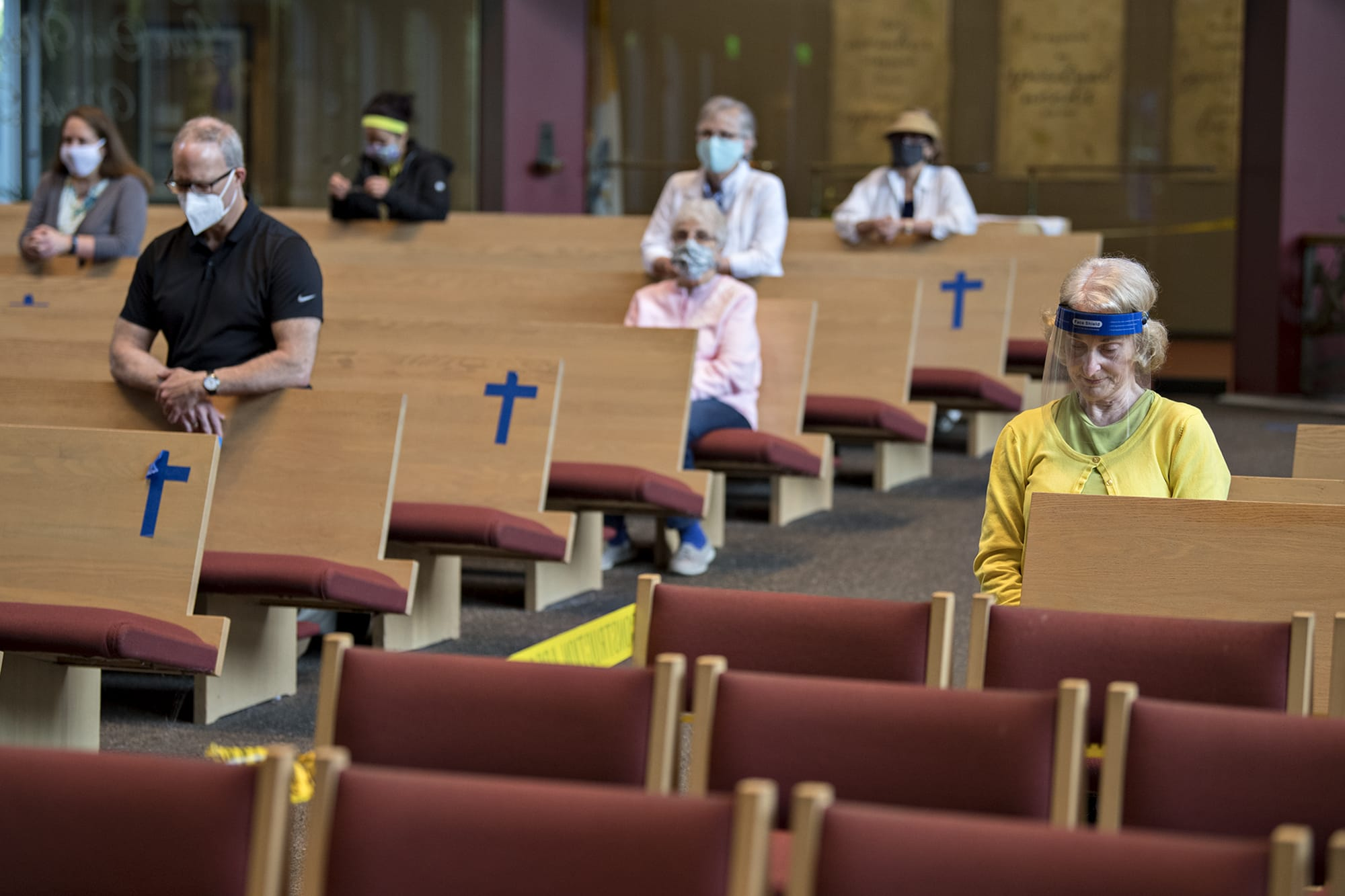 Connie Kessinger of St. Joseph Catholic Church, right, bows her head in prayer before the service on Thursday morning, June 18, 2020. As churches slowly reopen, the traditional Catholic Mass has shifted to adapt to COVID-19.