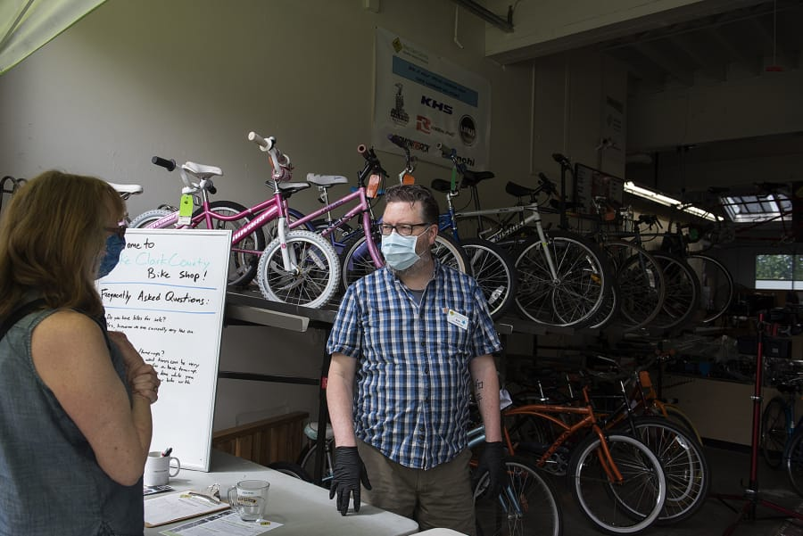 Vancouver resident Bev Warnock, left, talks with shop manager Eric Lien about repair for a bike at Bike Clark County on Wednesday morning. Bike sales have spiked during the COVID-19 pandemic.