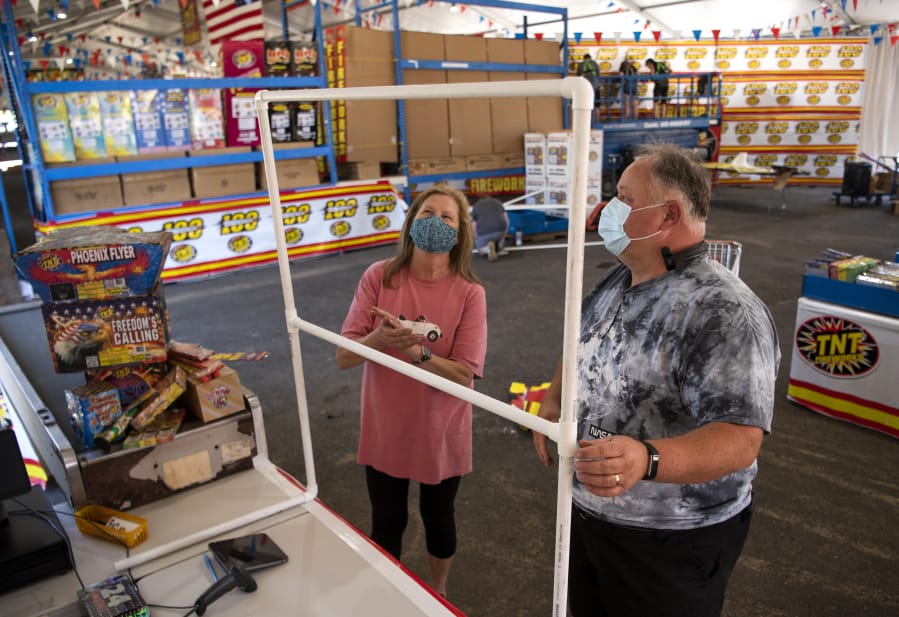 Cashier manager Charlotte Brown, left, and general manager Beau Leach describe the sneeze guards that will be set up at each register to protect employees at TNT Fireworks Warehouse in Hazel Dell. Leach said he went above the standard safety requirements and put extra steps in place to keep employees and customers safe. He ordered masks for customers to use for free if they do not have their own, as well as touchless hand sanitizer dispensers to place around the store.