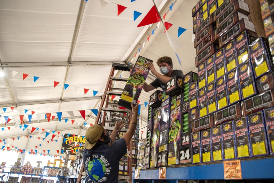 Assistant sales floor managers Cory Pena, left, and Skye Leach set up fireworks at TNT Fireworks Warehouse in Vancouver in June 2020.
