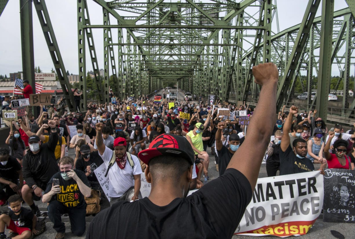 Hundreds of demonstrators take a knee for one minute to honor Black lives lost to police violence on the Interstate 5 bridge Friday afternoon, June 19, 2020.