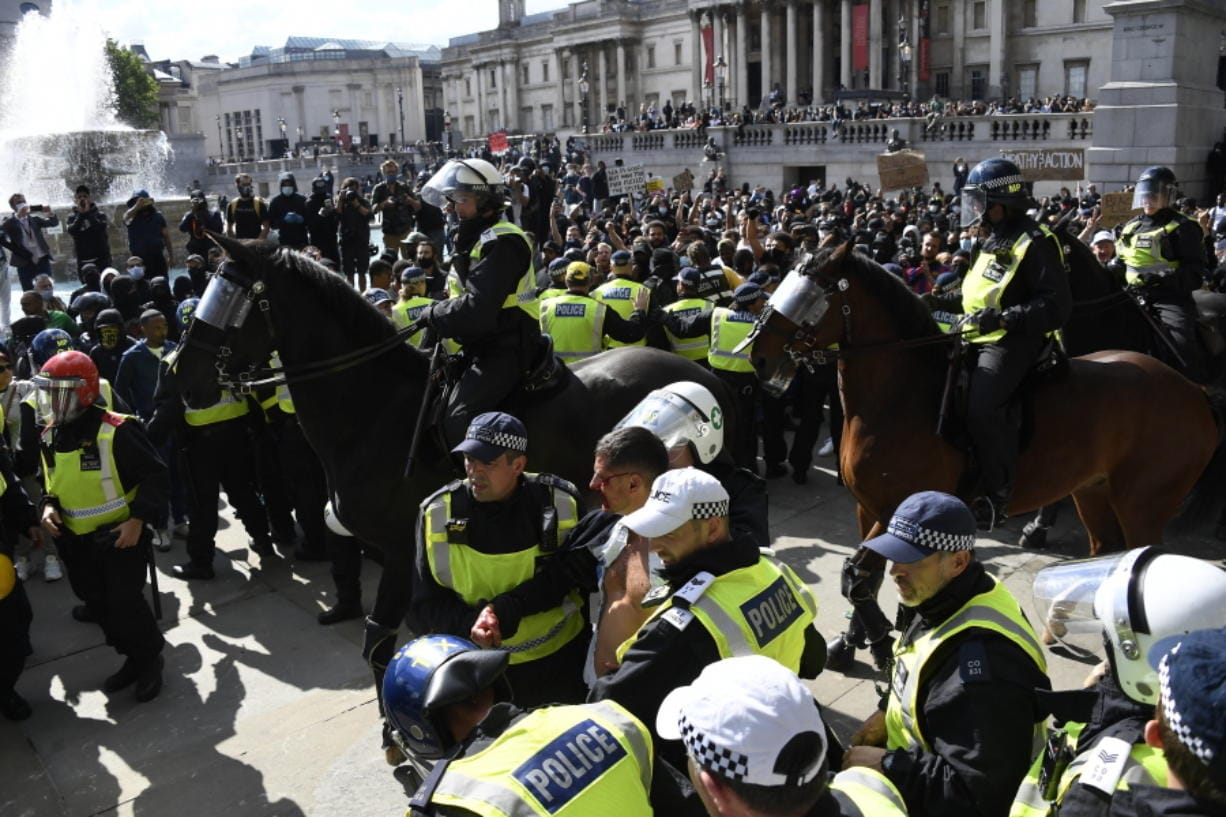 A wounded member of a far-right group is escorted by British police officers in riot gear, during scuffles as police tries to contain a protest at Trafalgar Square in central London, Saturday, June 13, 2020. British police have imposed strict restrictions on groups protesting in London Saturday in a bid to avoid violent clashes between protesters from the Black Lives Matter movement, as well as far-right groups that gathered to counter-protest.