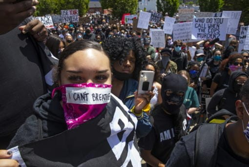 "A young woman with the words ""I can't breathe"" on her face covering joins thousands at a Black Lives Matter event in Eugene, Ore., Sunday May 31, 2020, over the deaths of George Floyd and others (Chris Pietsch/The Register-Guard via AP)"