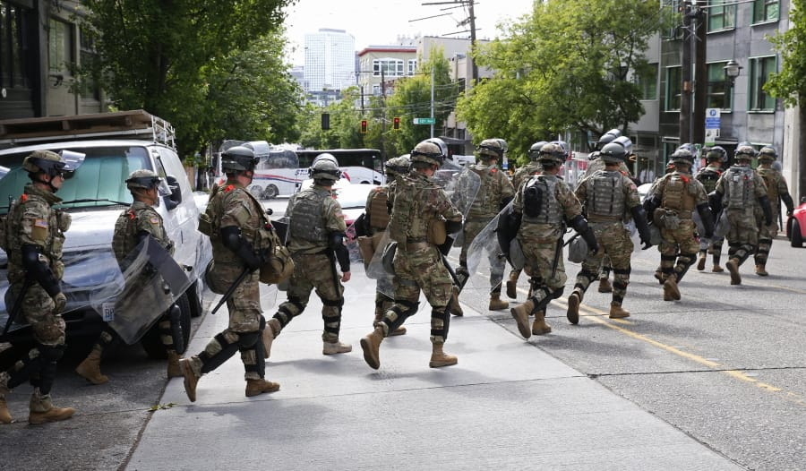 National Guard troops cross East Pike en route to the the East precinct of the Seattle Police Department, Monday, June 8, 2020, in Seattle's Capitol Hill neighborhood.