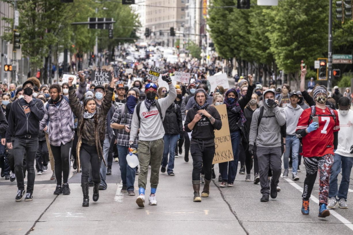 Protestors move south on 2nd Avenue in Seattle, Sunday, May 31, 2020, as demonstrations continue over the death of George Floyd. Floyd died after being restrained by Minneapolis police officers on May 25.