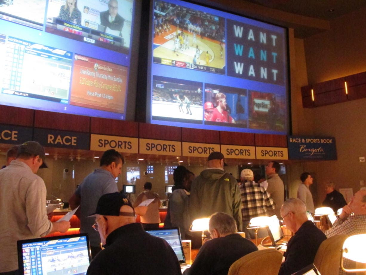 FILE - In this March 21, 2019 file photo, gamblers line up to place bets on the NCAA men's basketball tournament at the Borgata casino in Atlantic City N.J. After being closed since March due to the coronavirus outbreak, the Borgata will reopen to the general public on July 6, 2020, four days after much of its competition. Instead, the casino will be doing a test run for an invitation-only audience during those four days.