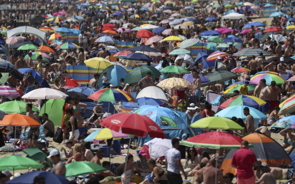 Crowds gather on the beach in Bournemouth, England, Thursday June 25, 2020, as coronavirus lockdown restrictions have been relaxed. According to weather forecasters Thursday could be the UK's hottest day of the year, so far, with scorching temperatures forecast to rise even further.