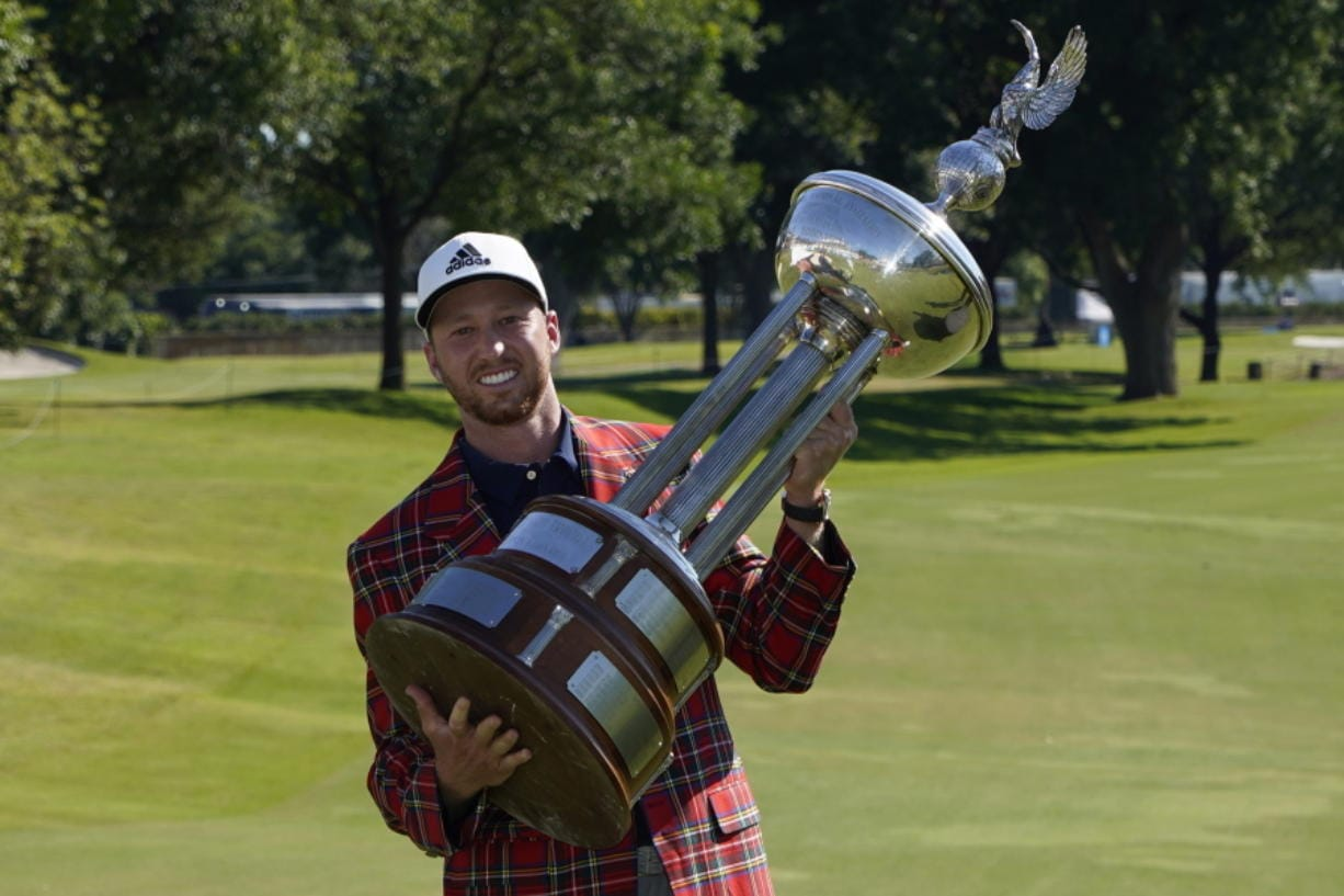 Daniel Berger poses with the championship trophy after winning the Charles Schwab Challenge golf tournament after a playoff round at the Colonial Country Club in Fort Worth, Texas, Sunday, June 14, 2020. (AP Photo/David J.