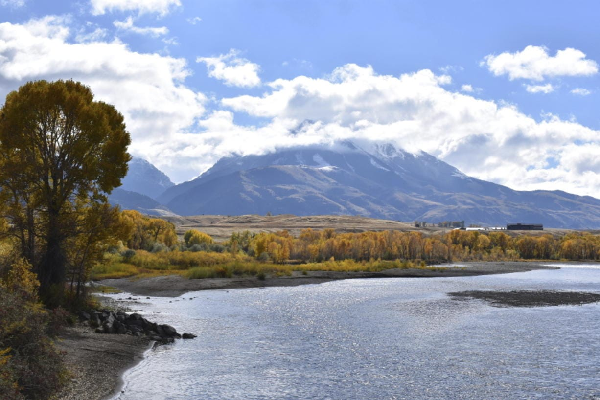 FILE - In this Oct. 8, 2018 file photo, emigrant Peak is seen rising above the Paradise Valley and the Yellowstone River near Emigrant, Mont. Lawmakers have reached bipartisan agreement on an election-year deal to double spending on a popular conservation program and devote nearly $2 billion a year to improve and maintain national parks.
