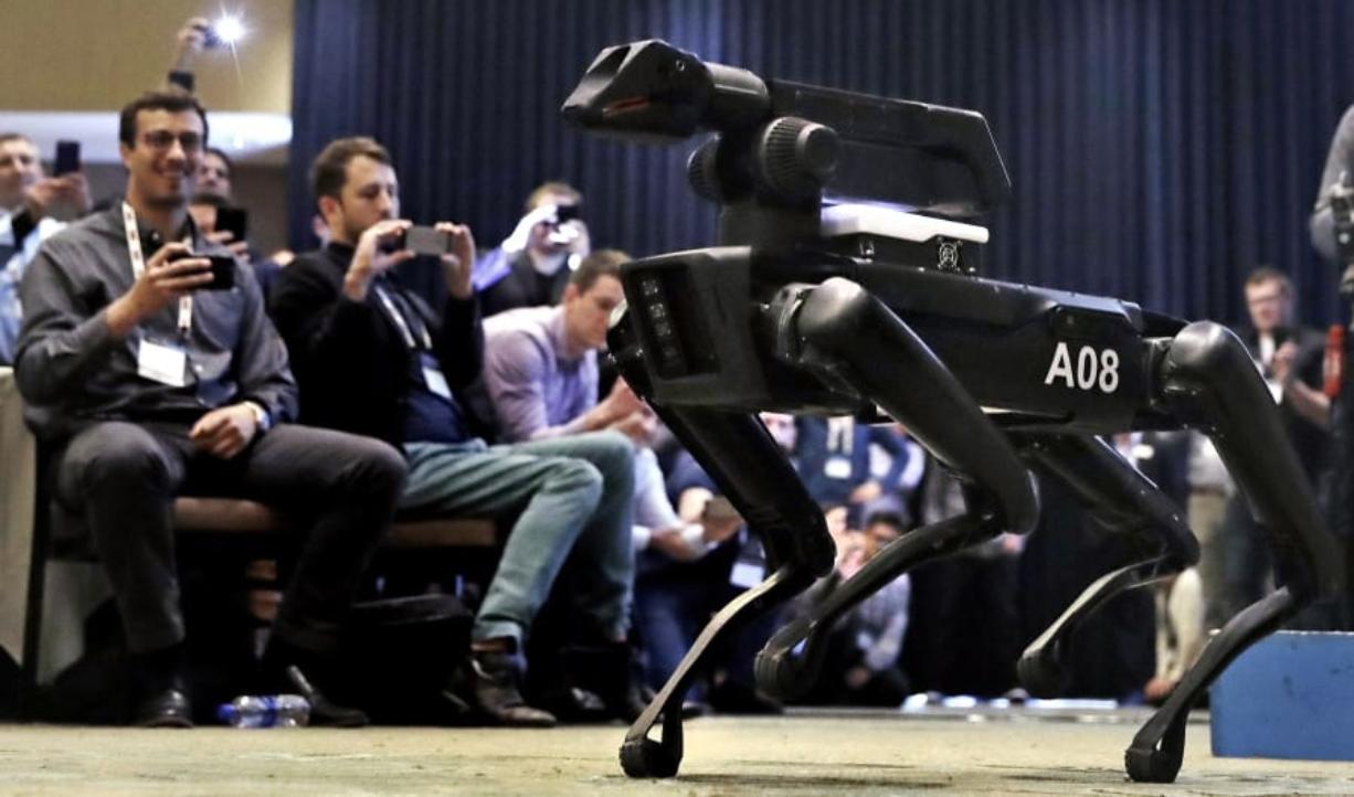 A Boston Dynamics SpotMini robot walks through a conference room during a robotics summit in Boston.