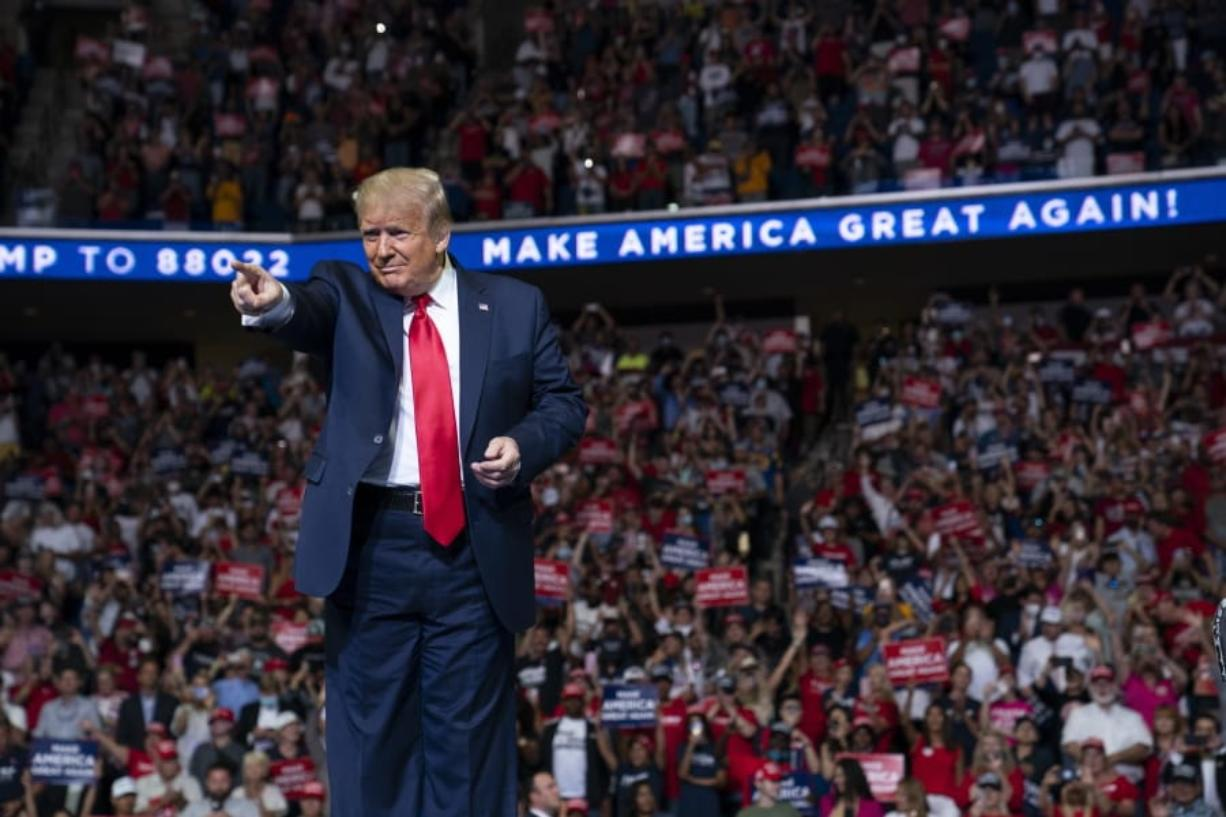 In this June 20, 2020, photo, President Donald Trump arrives on stage to speak at a campaign rally at the BOK Center in Tulsa, Okla.