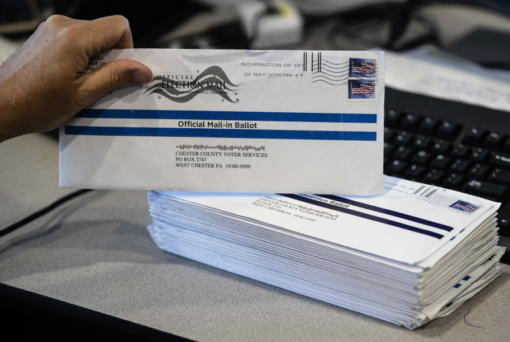In this May 28, 2020, photo, Dave Turnier processes mail-in ballots at at the Chester County Voter Services office in West Chester, Pa., prior to the primary election. Tuesday's primary elections in seven states are both significant elections and big tests of campaigning during the age of coronavirus.