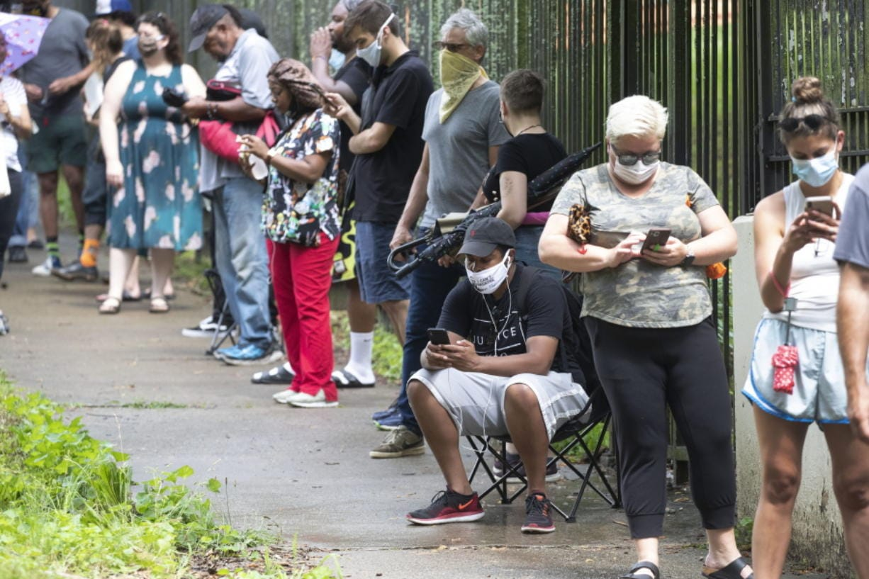 FILE - In this June 9, 2020, file photo, Steven Posey checks his phone as he waits in line to vote at Central Park in Atlanta. Voters reported wait times of three hours. When some Georgia voters endured a pandemic, pouring rain and massive waits earlier this month to cast their ballot, President Donald Trump and other Republicans blamed local Democrats for presiding over chaos.