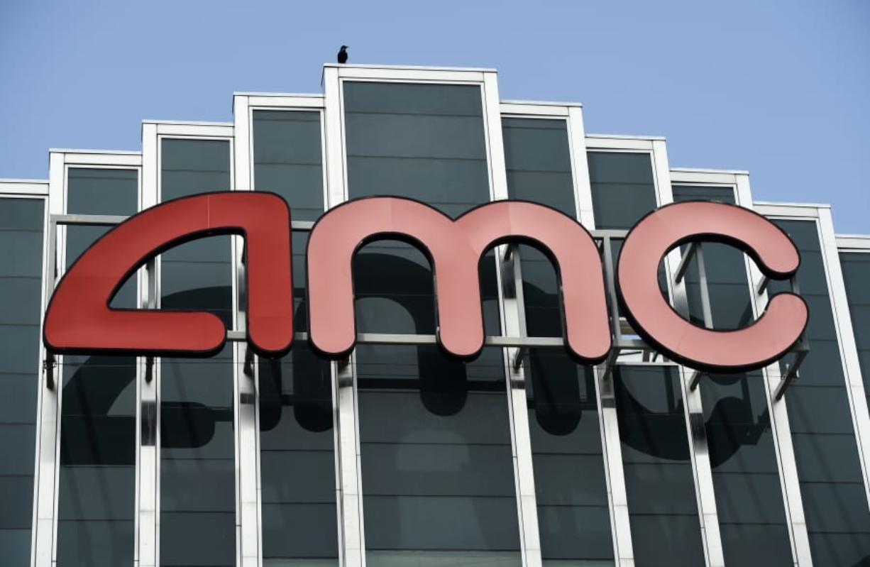 FILE - In this April 29, 2020 file photo, the AMC sign appears at AMC Burbank 16 movie theater complex in Burbank, Calif. AMC Theaters, the nation's largest chain, is pushing back its plans to begin reopening theaters by two weeks. The company said Monday that it would open approximately 450 U.S. locations on July 30 and the remaining 150 the following week.
