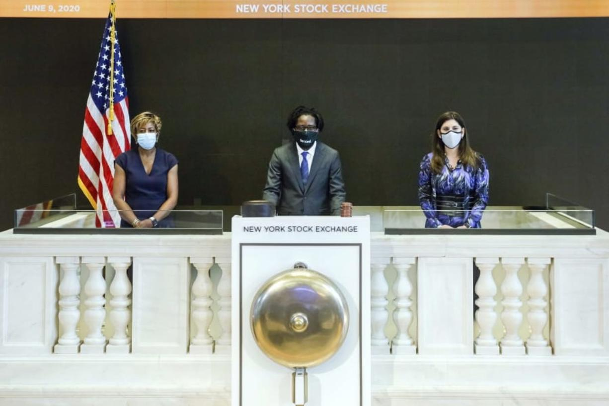 In this photo taken from video provided by the New York Stock Exchange, Frederick Baba, center, managing director Goldman Sachs, accompanied by NYSE President Stacey Cunningham, right, and Intercontinental Exchange Board member Sharon Bowen, rings a single strike of the New York Stock Exchange bell in tribute to the life of George Floyd, initiating eight minutes and forty-six seconds of silence to coincide with the start of Mr. Floyd's funeral, Tuesday June 9, 2020.