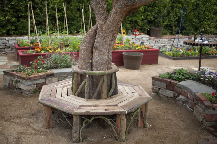 A bench around a tree and raised flower and vegetable beds.