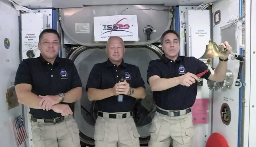 In this image taken from NASA video NASA astronaut Chris Cassidy, right, rings the opening bell of the New York Stock Exchange as fellow astronauts Robert L. Behnken, left, and Chris Cassidy right, listen Tuesday, June 2, 2020, in the International Space Station.