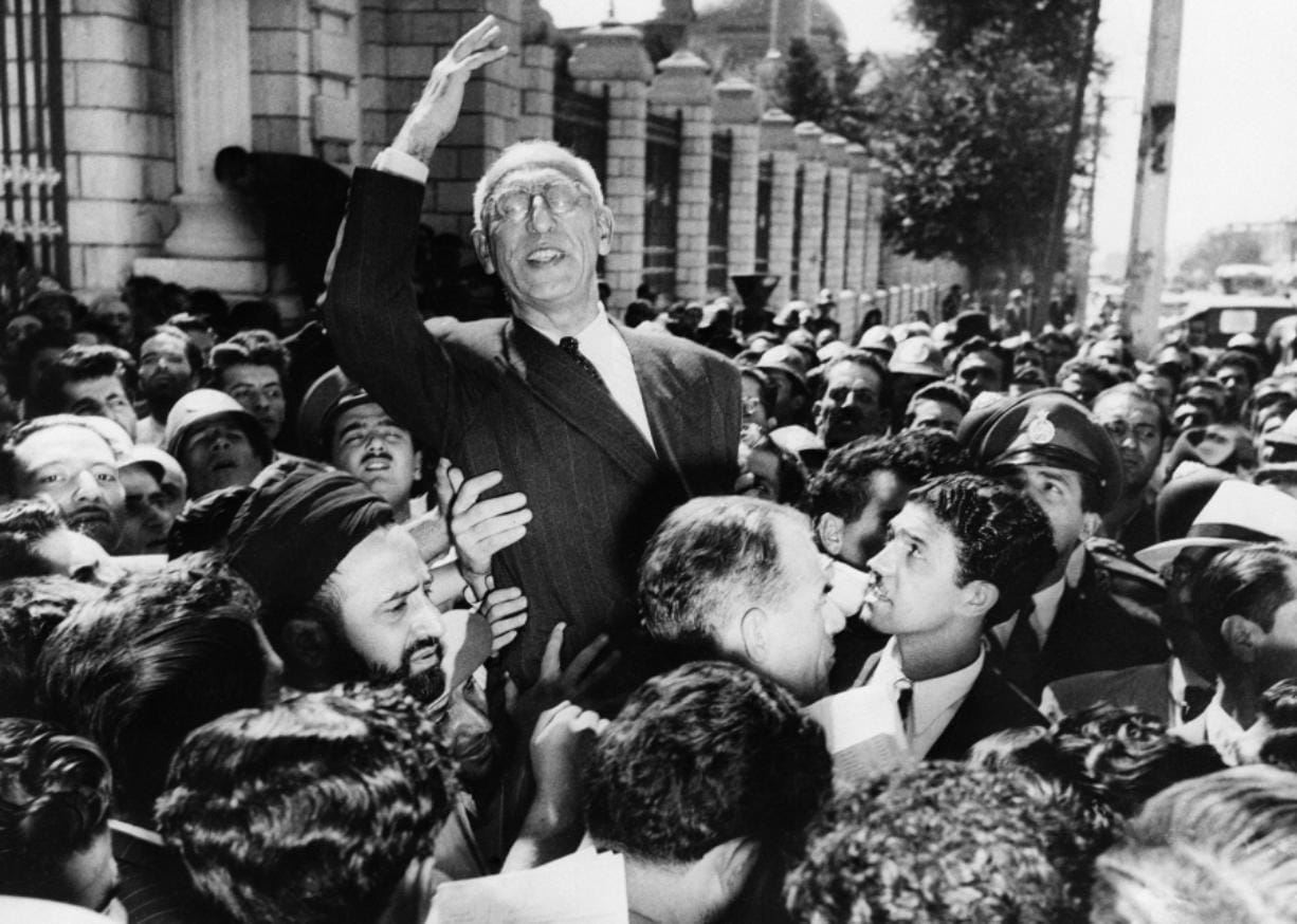 FILE - In this Sept. 27, 1951 file photo, Prime Minister Mohammad Mosaddegh rides on the shoulders of cheering crowds in Tehran's Majlis Square, outside the parliament building, after reiterating his oil nationalization views to his supporters. The U.S. ambassador to Iran mistakenly told the shah in 1953 that Britain's newly enthroned Queen Elizabeth II backed a plan to overthrow the country's elected prime minister and America maintained the fiction even after realizing the error, historians now say.