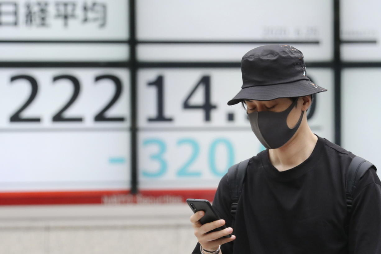 A man walks by an electronic stock board of a securities firm in Tokyo, Thursday, June 25, 2020. Shares declined in Asia on Thursday after a sharp retreat overnight on Wall Street as new coronavirus cases in the U.S. climbed to their highest level in two months, dimming investors' hopes for a relatively quick economic turnaround.