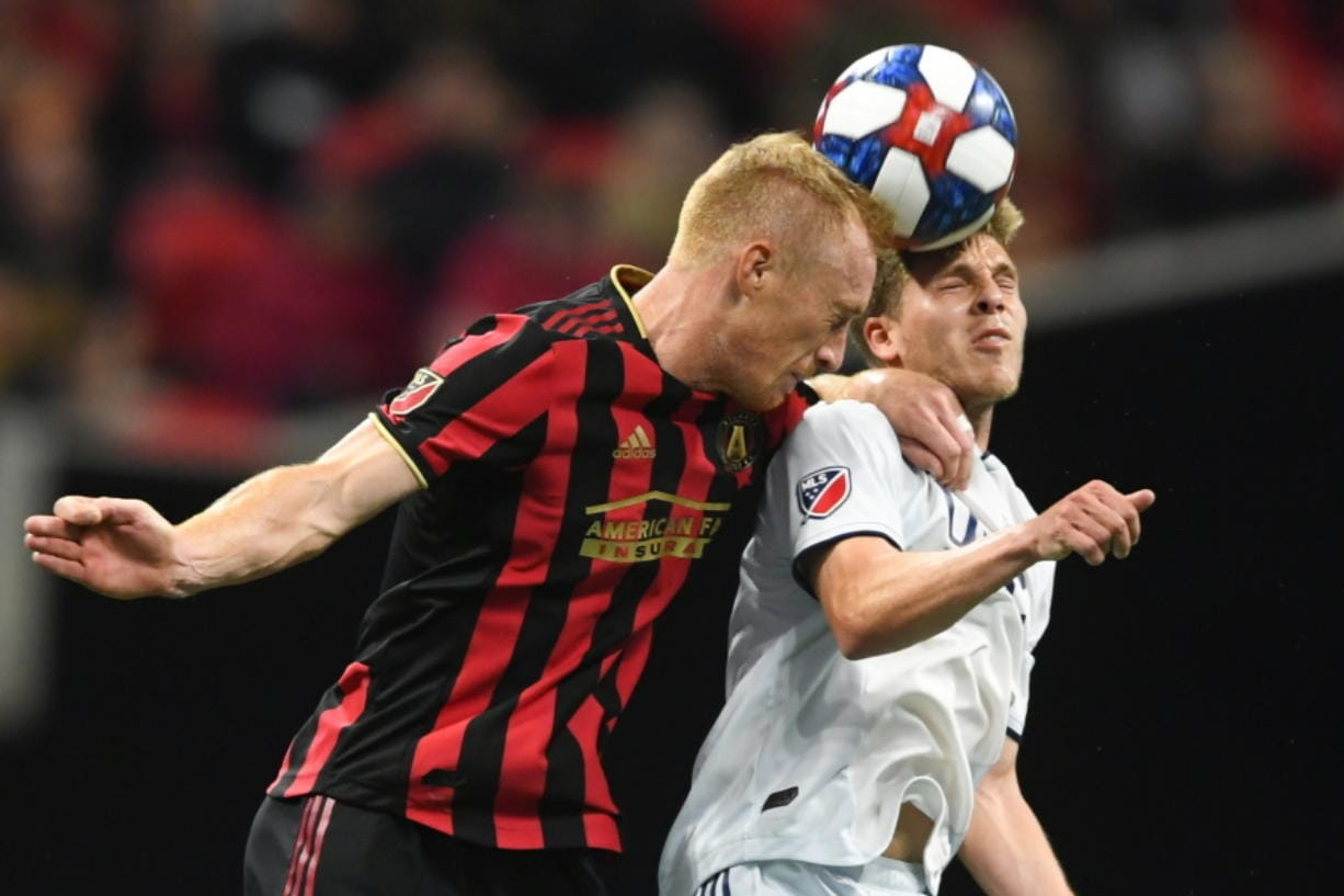 FILE - In this Oct. 19, 2019, file photo, Atlanta United defender Jeff Larentowicz, left, and New England Revolution midfielder Scott Caldwell battle for a header during round one of an MLS Cup playoff soccer game in Atlanta. Atlanta United veteran defender Jeff Larentowicz, who serves as an executive board member for the players union, said Thursday, June 4, 2020, he has safety concerns about an agreement announced Wednesday for a MLS tournament in Orlando in July.