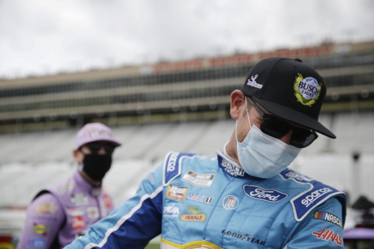 Kyle Busch, left, and Clint Bowyer, right, laugh on pit row before a NASCAR Cup Series auto race at Atlanta Motor Speedway on Sunday, June 7, 2020, in Hampton, Ga.