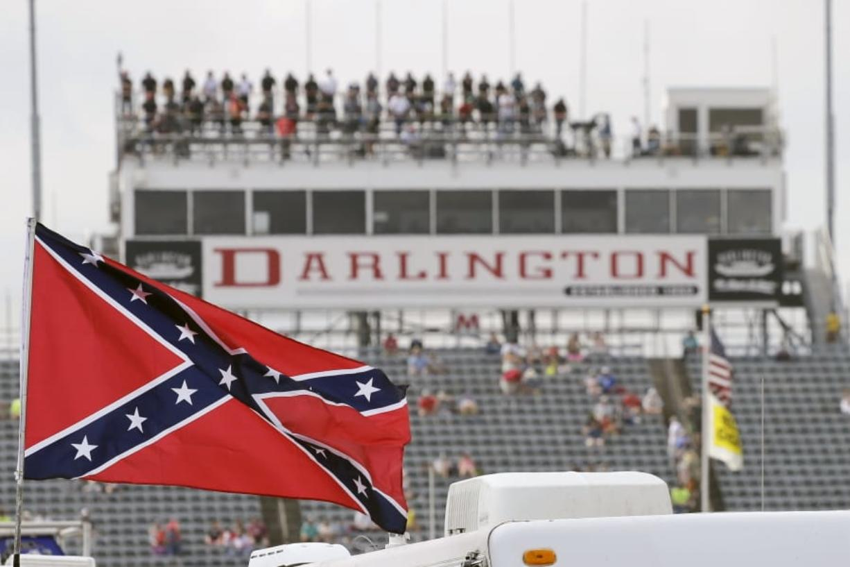 FILE - In this Sept. 5, 2015, file photo, a Confederate flag flies in the infield before a NASCAR Xfinity auto race at Darlington Raceway in Darlington, S.C. Bubba Wallace, the only African-American driver in the top tier of NASCAR, calls for a ban on the Confederate flag in the sport that is deeply rooted in the South.