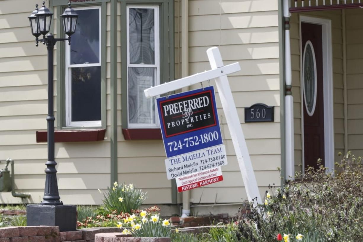 This April 16, 2020 photo shows a real estate company sign that marks a home for sale in Harmony, Pa.  U.S. new home sales plunged 15.4% in March as the lockdowns that began in the middle of the month began to rattle the housing market.