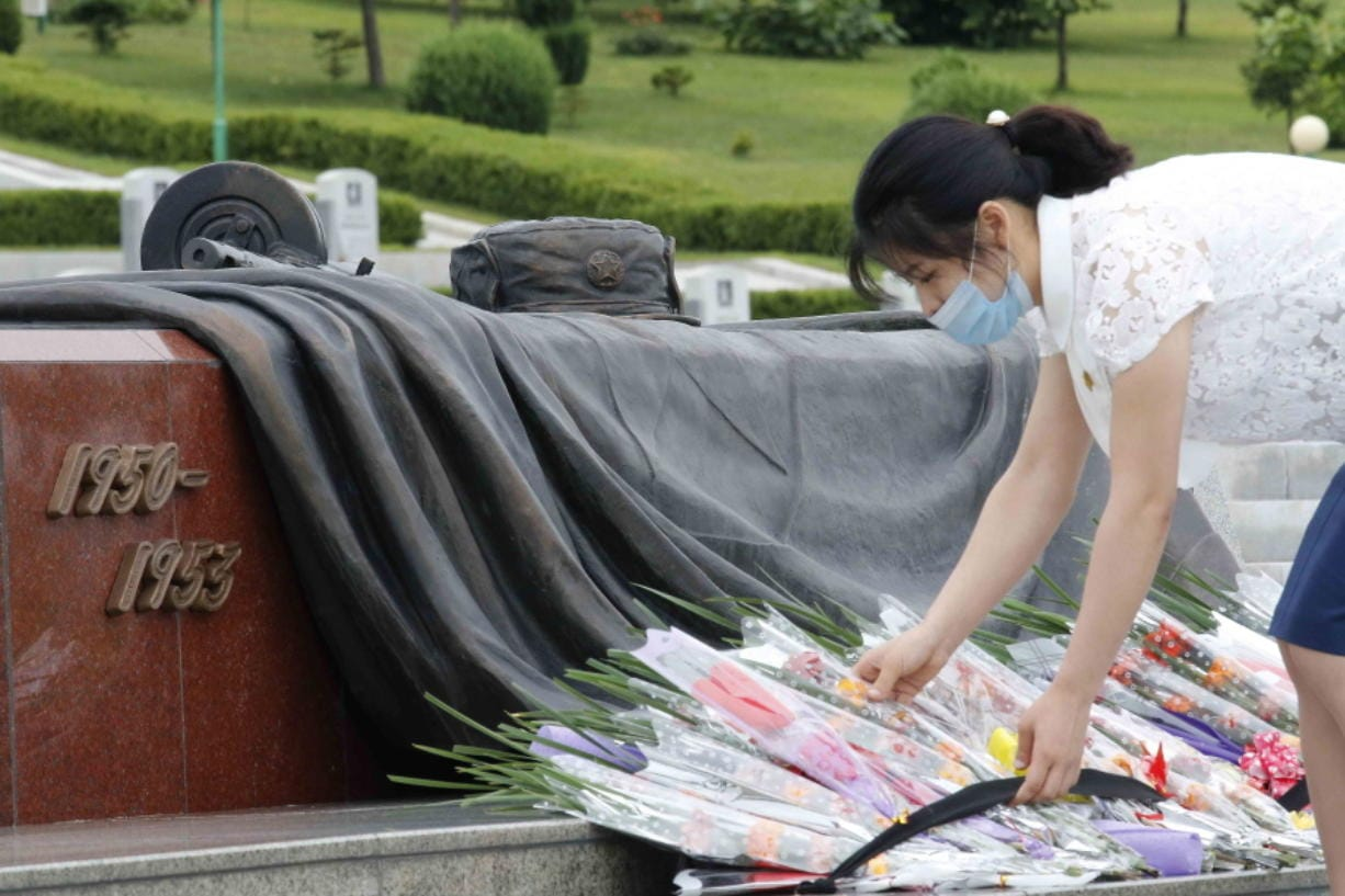 A North Korean woman lays a bouquet of flowers during a visit to the Fatherland Liberation War Martyrs Cemetery to pay respects to the monument to the fallen soldiers of the Korean People's Army in Pyongyang, North Korea, Thursday, June 25, 2020. North and South Korea on Thursday marked the 70th anniversary of the start of the Korean War with largely subdued commemorations amid the coronavirus pandemic, a day after the North abruptly halted a pressure campaign against the South.