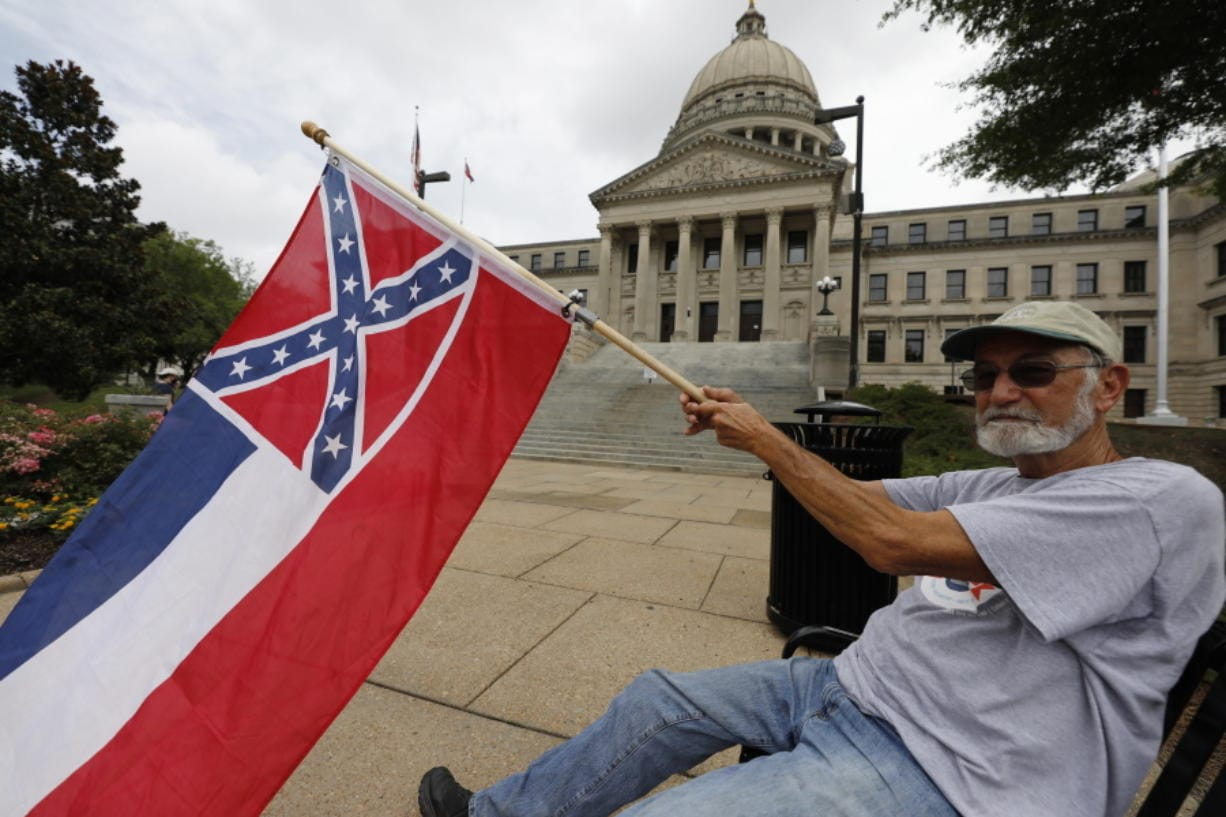 Larry Eubanks of Star waves the current Mississippi state flag as he sits before the front of the Capitol, Saturday, June 27, 2020, in Jackson, Miss. While a supporter of the current flag, Eubanks says he would hope lawmakers would allow a proposed flag change to be decided by the registered voters. The current state flag has in the canton portion of the banner the design of the Civil War-era Confederate battle flag, that has been the center of a long-simmering debate about its removal or replacement. (AP Photo/Rogelio V.